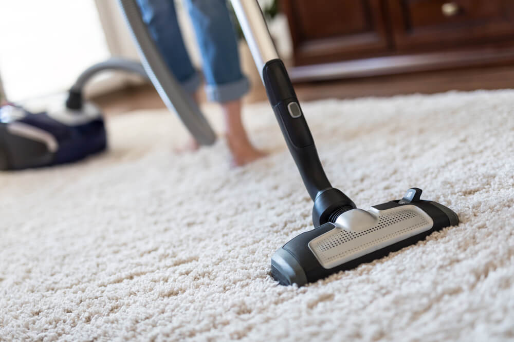 絨毯を掃除機で掃除する女性