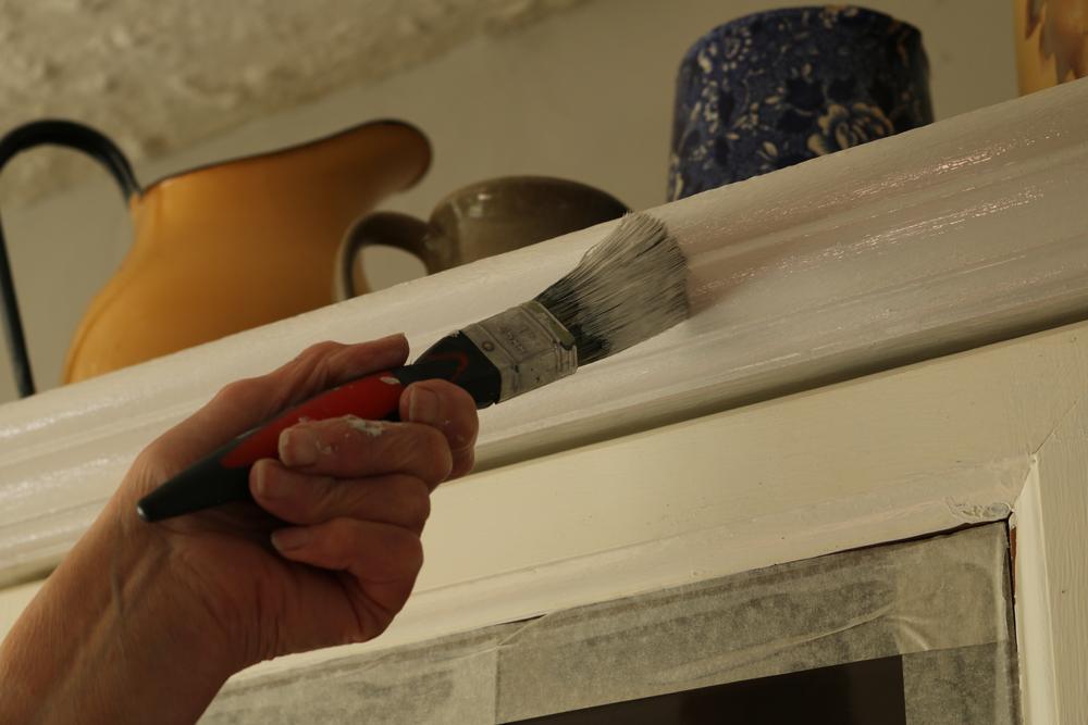 食器棚を塗る女性