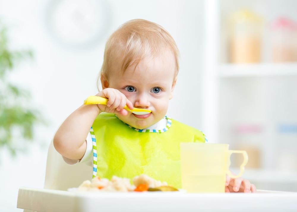 ベビーチェアで食事する子供