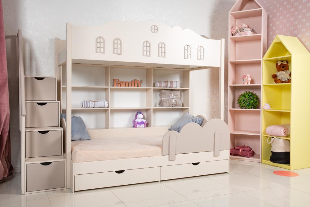 白い2段ベッドとカラフルな棚がある子ども部屋