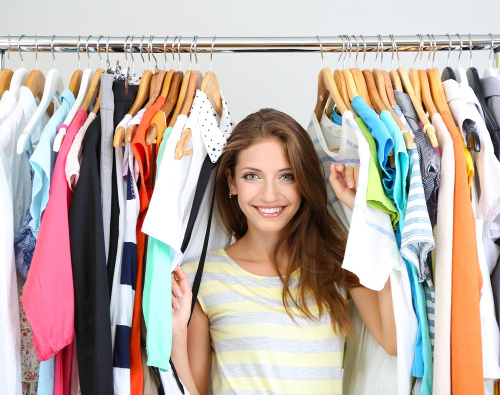 たくさんの洋服の間で笑顔を浮かべる女性
