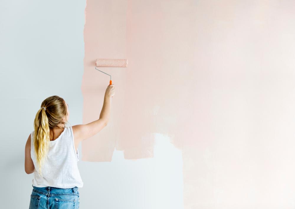 壁にペンキを塗る女性