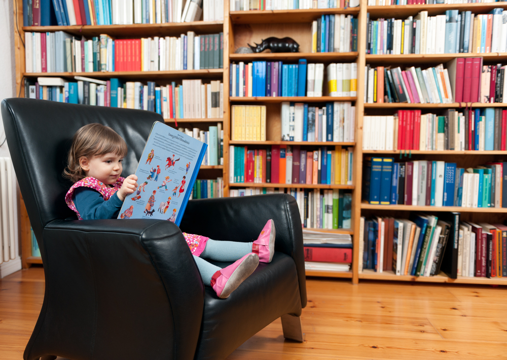 ソファーに座りながら絵本を読む女の子