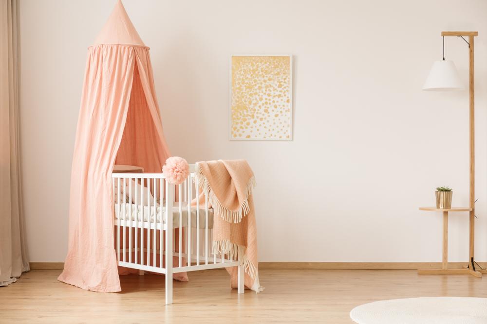 ピンクのカーテンがついたベビーベッド