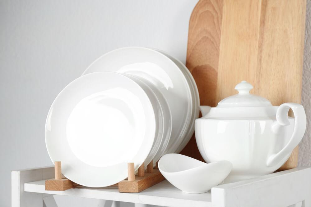 棚の上に置かれた白い食器と木のまな板