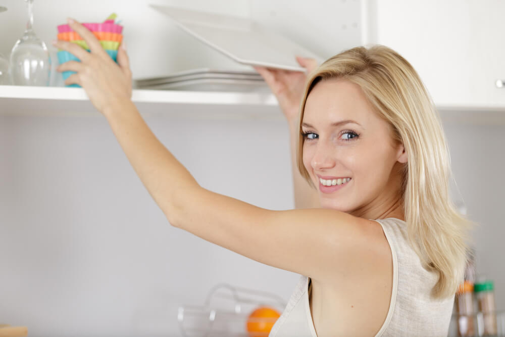 食器を棚に置きながら笑顔を浮かべる女性
