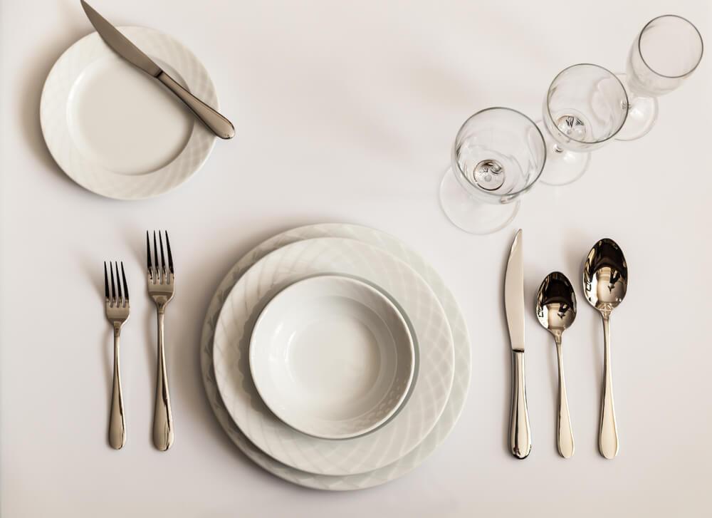 白い食器とカトラリーが並んだテーブル