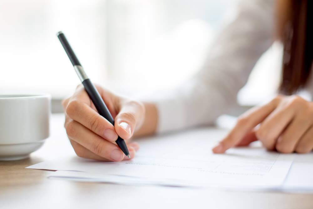 ボールペンで書類を書く女性