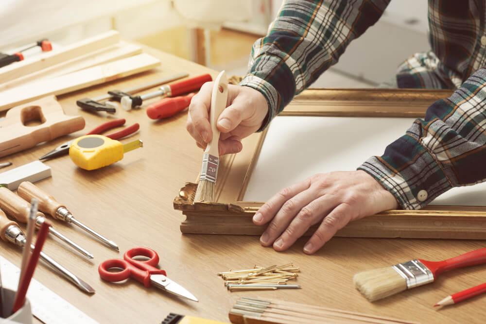 作業台の上で木枠をペイントする男性