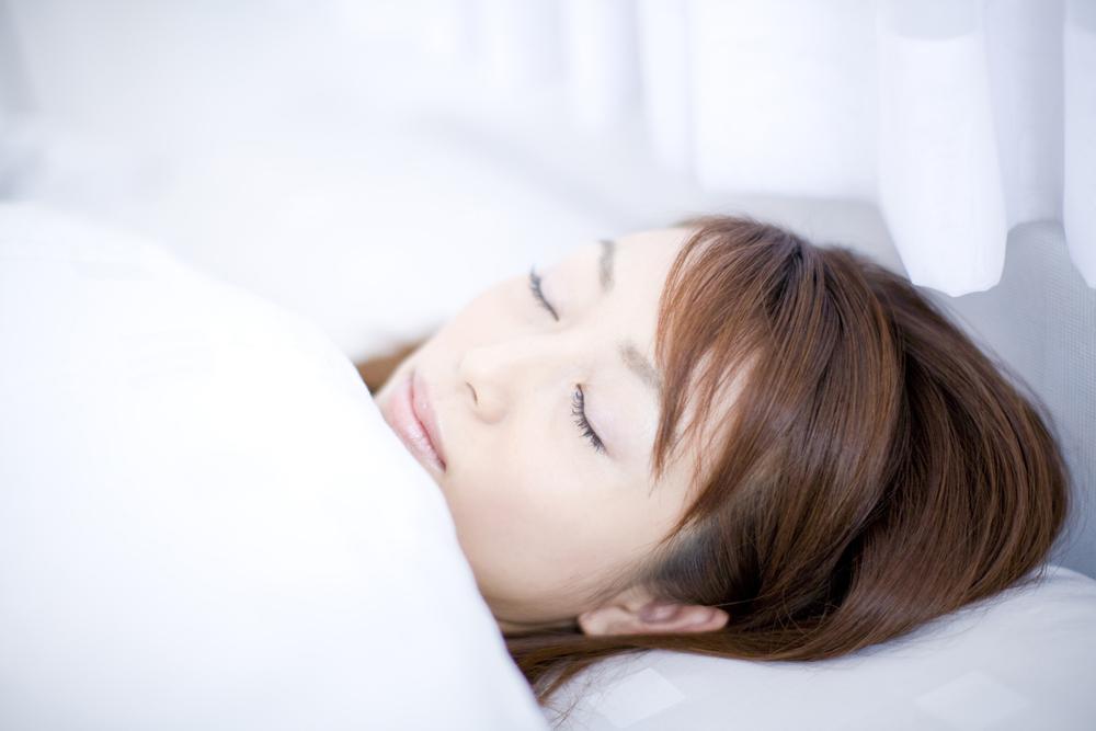 白いふとんで眠る女性