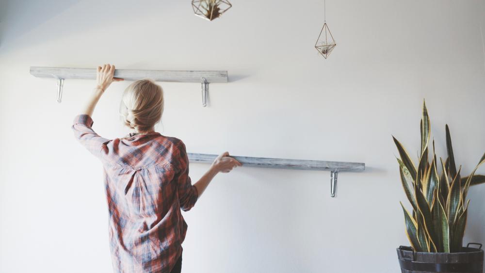 壁に棚を掛ける女性