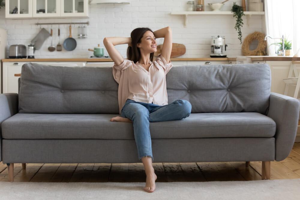 笑顔でソファに座る女性