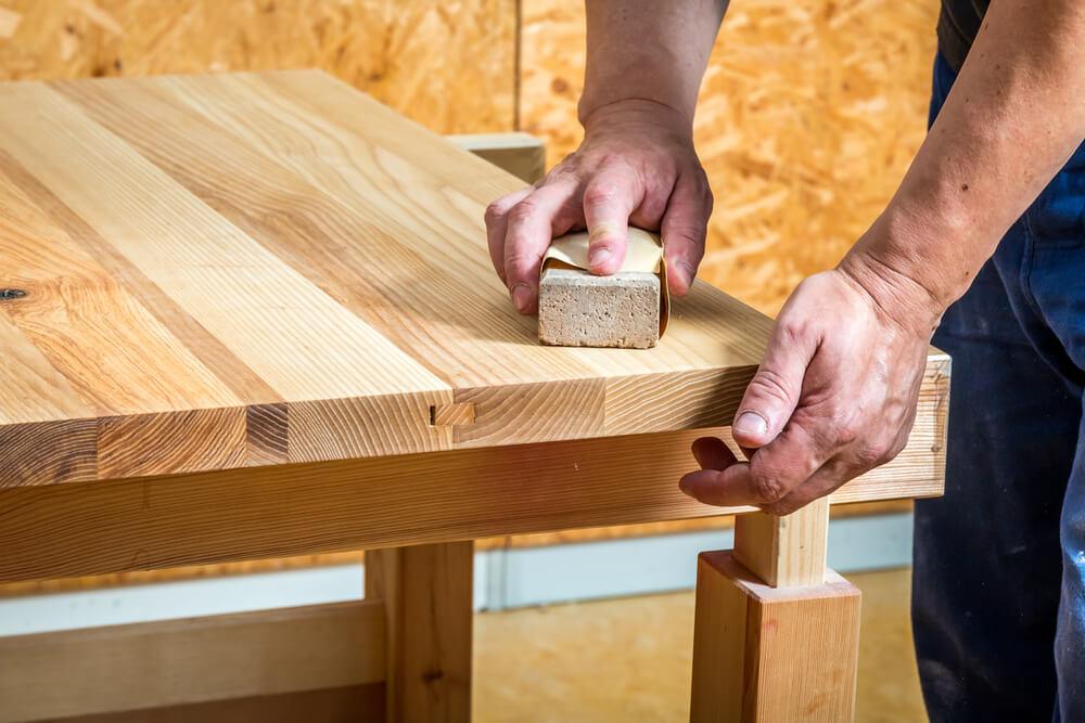 テーブルの天板に紙やすりを掛ける男性