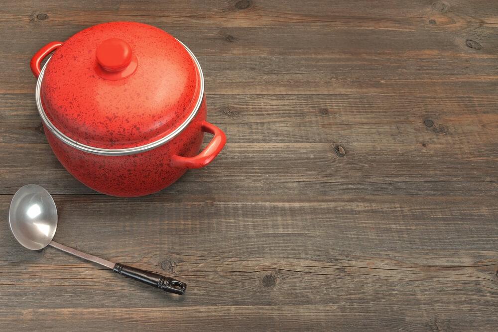 お玉と一緒に置かれた赤いホーロー鍋