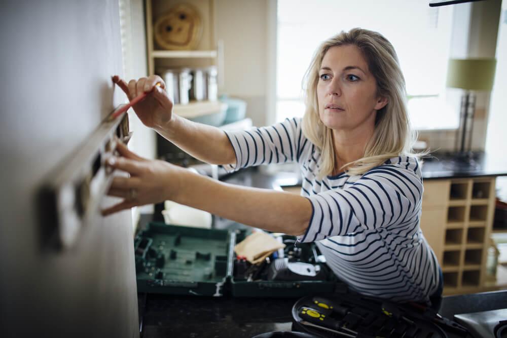 壁に鉛筆で印を付ける女性
