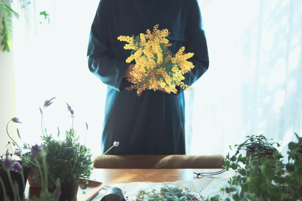黄色い花を束ねる女性