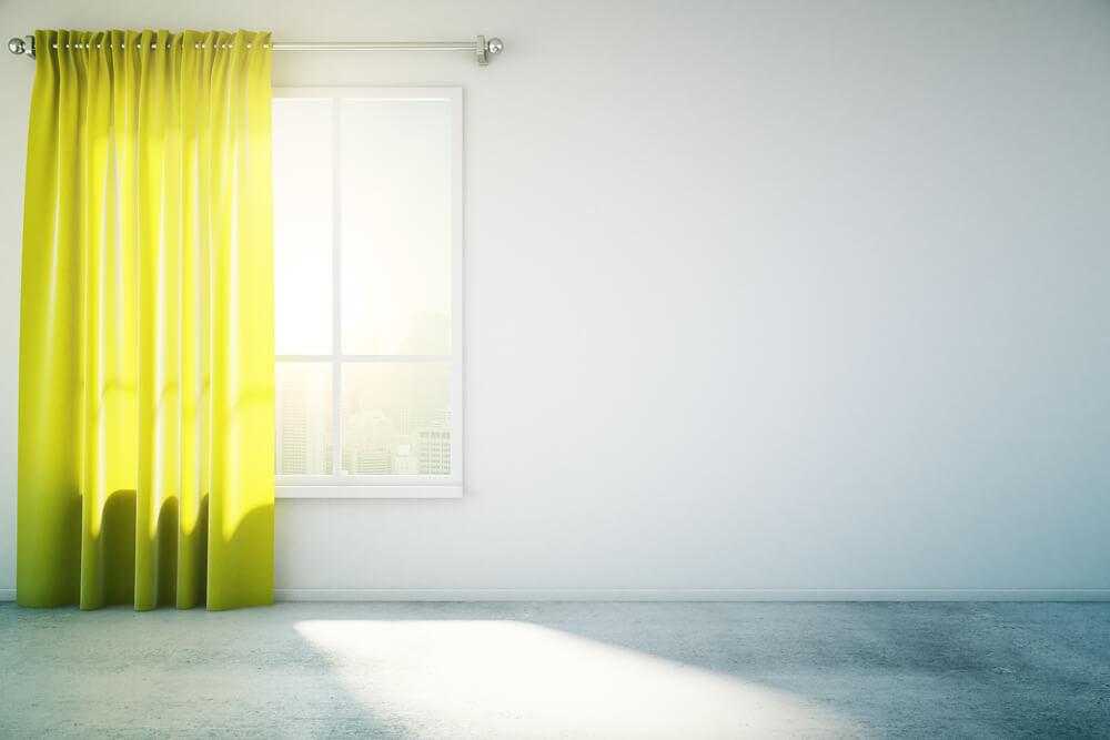 カーテンの間から光が差し込む部屋