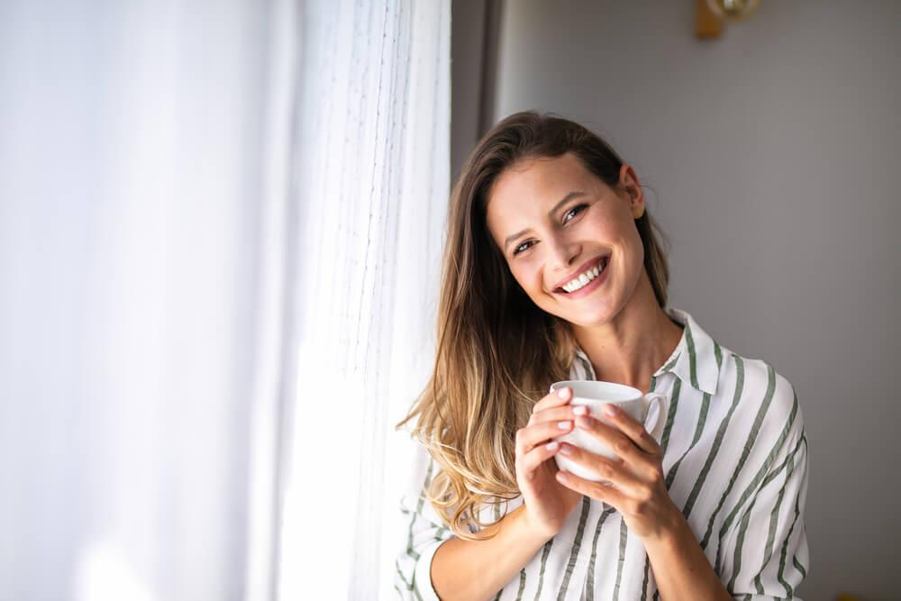 カップを持って笑顔を浮かべる女性