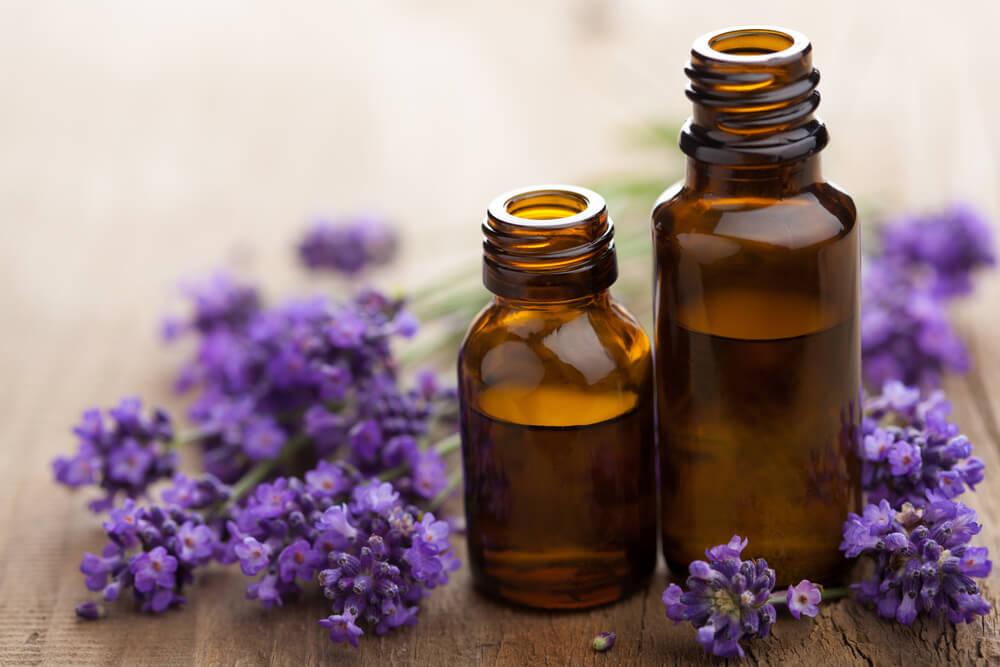 紫色の花と蓋が開いたアロマオイルのボトル