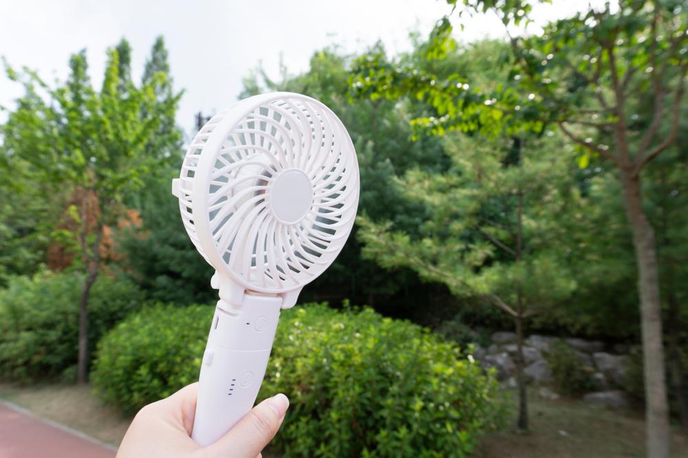 外でハンディ扇風機を使う人