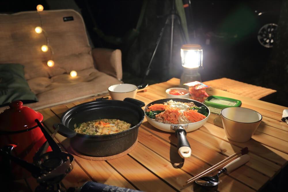 木製テーブル上の料理とキャンプ用ランタン
