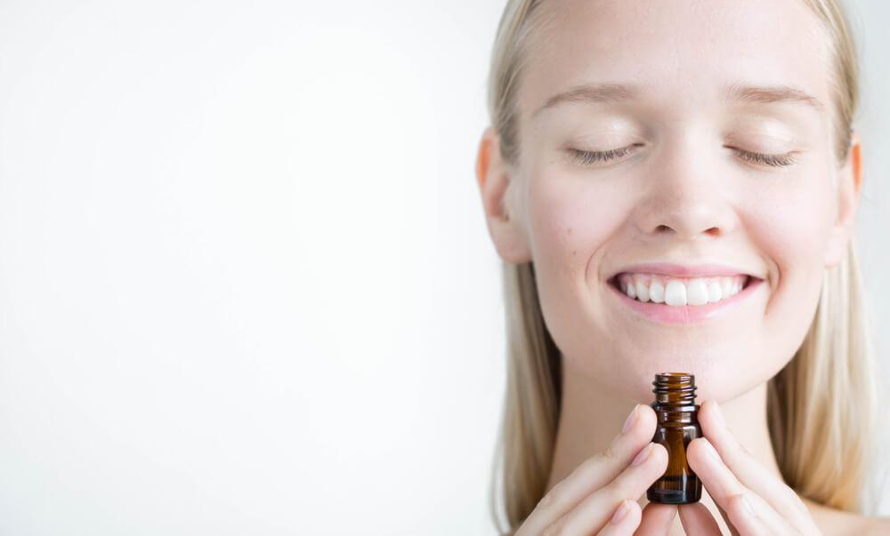 精油のボトルを持って笑顔を浮かべる女性
