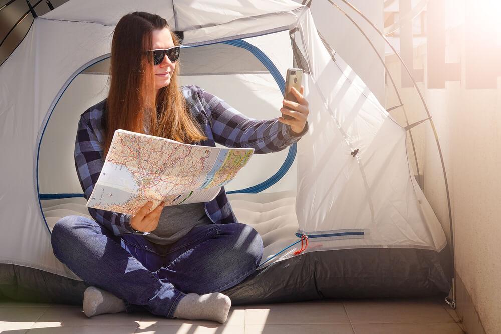 ベランダに張ったテントで写真を撮る女性