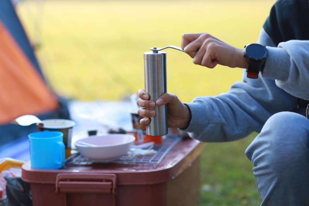 ミルでコーヒー豆を挽く人の手元