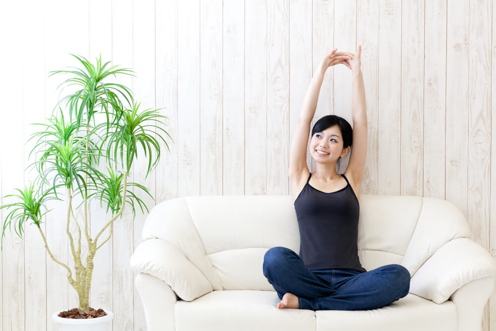 ソファの上で背伸びをする女性