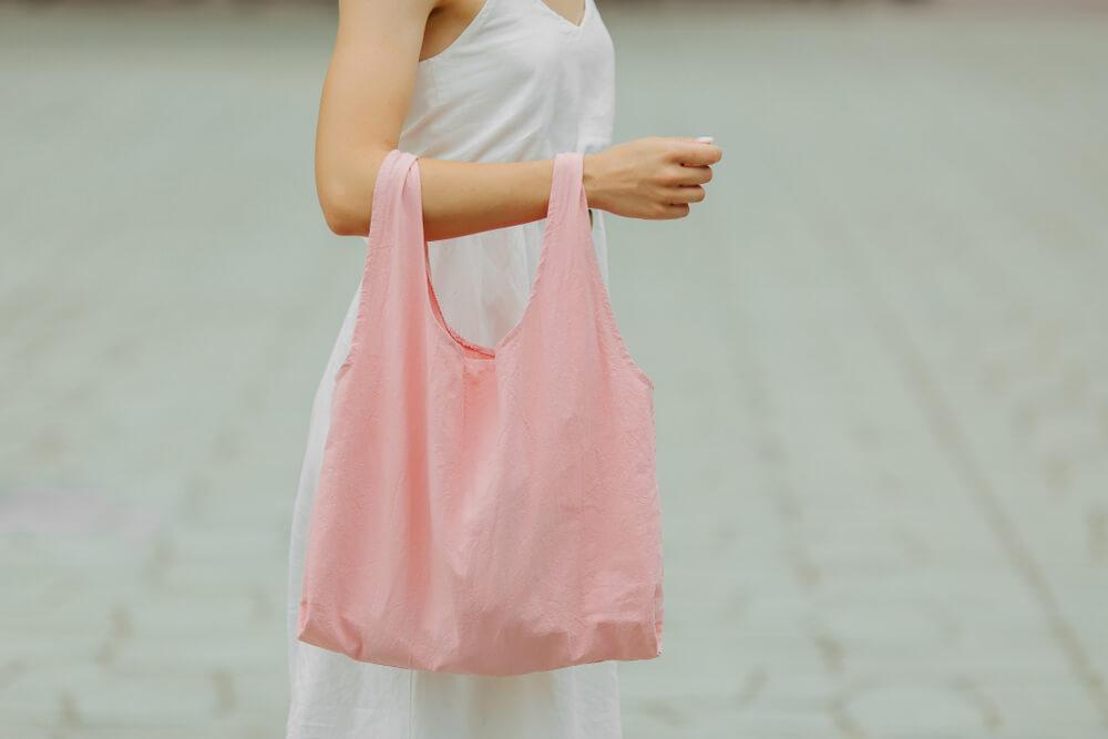 ピンクの小さいエコバッグを持つ女性