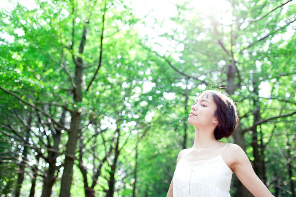 森の中でリラックスする女性