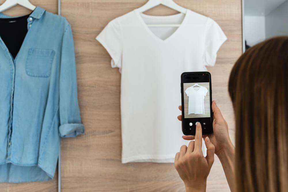 携帯で服の写真を撮る女性