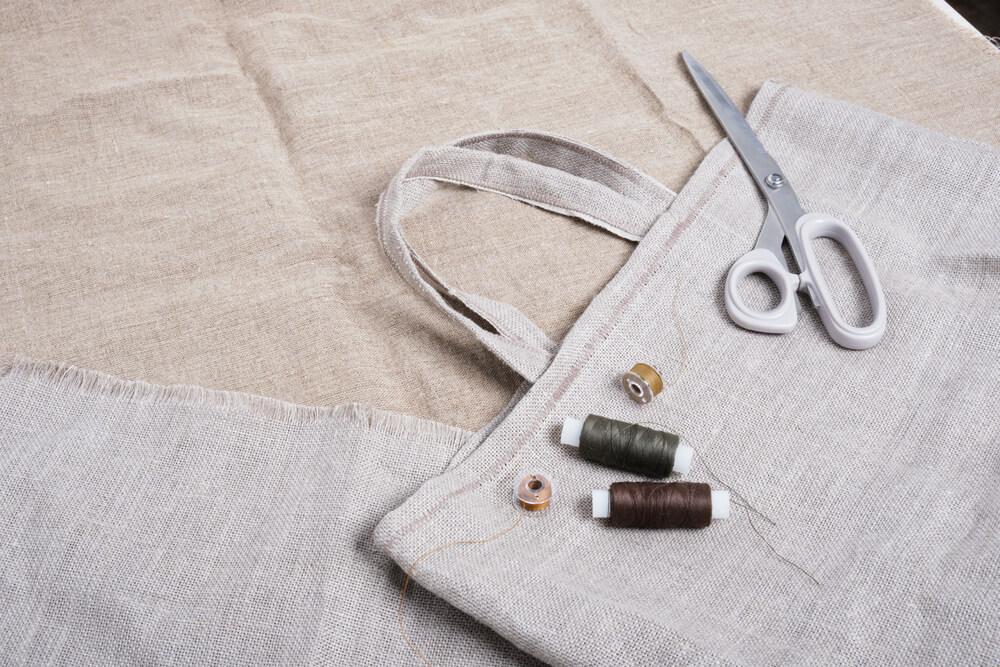 リネン生地のエコバッグとハサミと糸