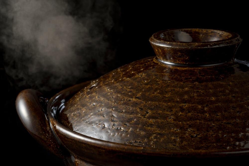 湯気が出ている黒い土鍋