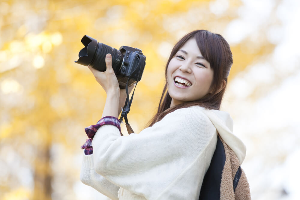 笑顔でカメラを持つ女性