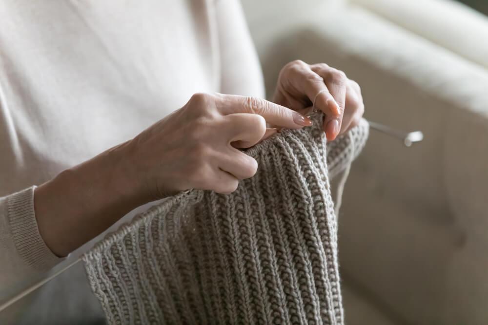 グレーの毛糸で編み物をする人