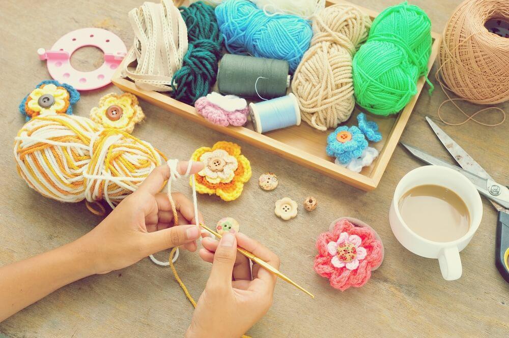 カラフルな毛糸でかぎ針編みをする人