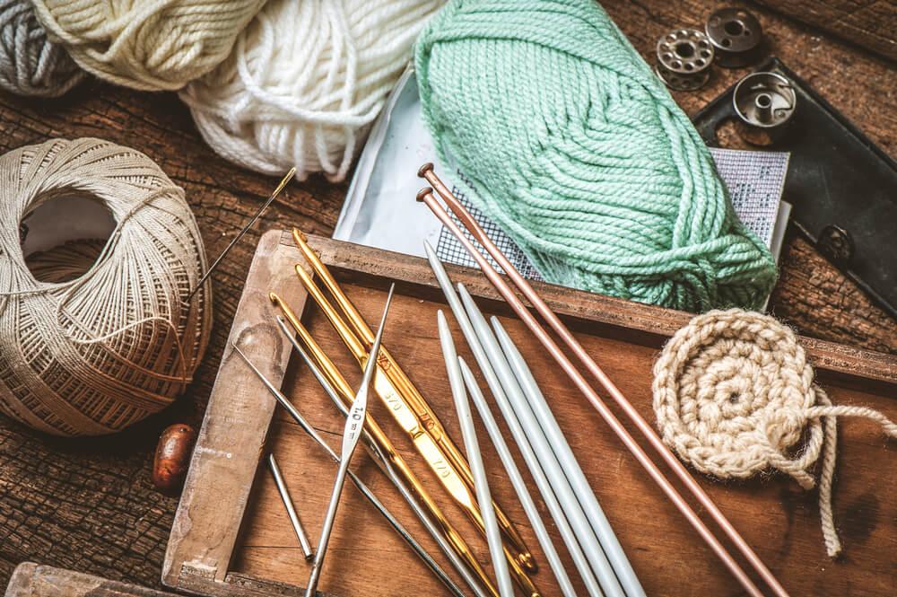テーブルに並んだ編み針や毛糸