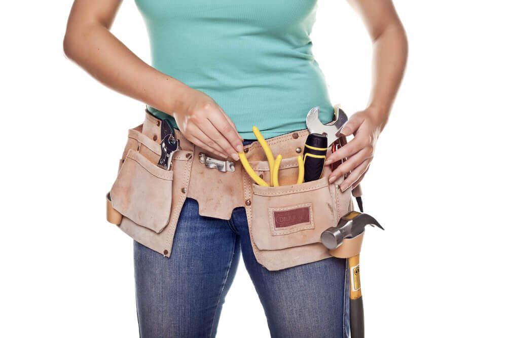 工具用ベルトに工具を入れる女性