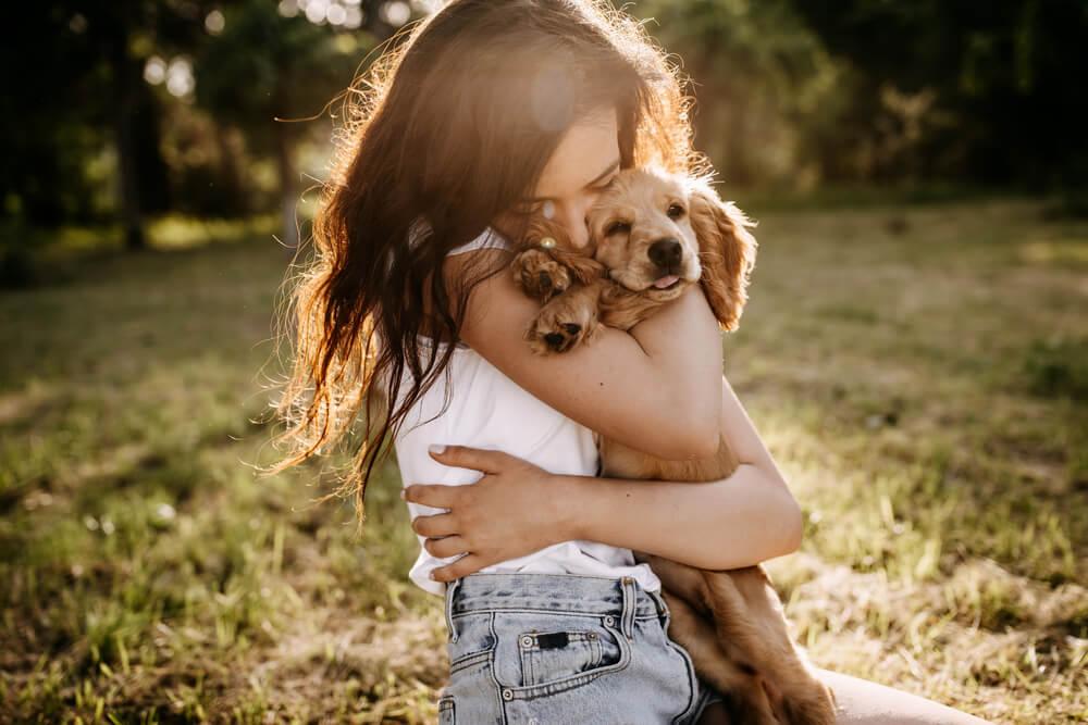 子犬を抱きしめる女性