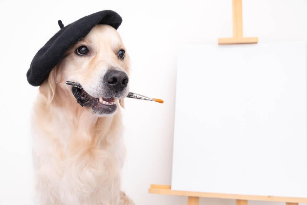 筆を加えてキャンパスの前に座る犬