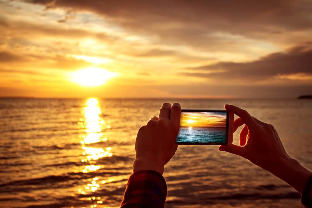 夕陽が沈む海の写真を撮っている人